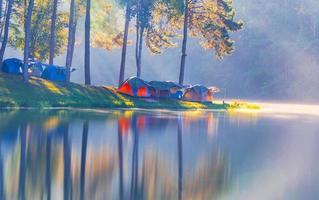 avventure campeggio turismo e tenda sotto la foresta di pini con riflesso sull'acqua al mattino a pang-ung, mae hong son, thailandia foto