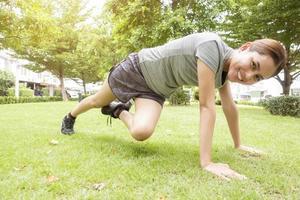 bella donna sportiva sta facendo esercizi nel parco verde green foto