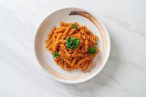 pasta a spirale o spirali con salsa di pomodoro e salsiccia - stile italiano foto