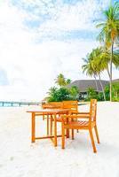 tavolo e sedia in legno vuoto sulla spiaggia con sfondo vista mare alle maldive foto