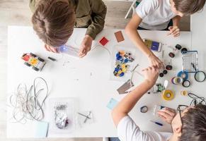giovani ragazzi e insegnanti che si divertono a costruire auto robot in officina, vista dall'alto foto