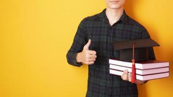 l'uomo dell'università è felice della laurea su sfondo giallo foto