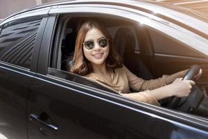 la bella donna sta guidando la sua macchina foto
