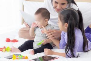 giovane madre asiatica e bambina sdraiata e giocando insieme sul letto, mamma e figlia, famiglia di emozione ed espressione con felice, genitore e neonato relax e positivo, emozione ed espressione. foto