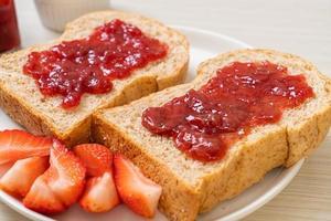 pane integrale fatto in casa con marmellata di fragole e fragole fresche foto