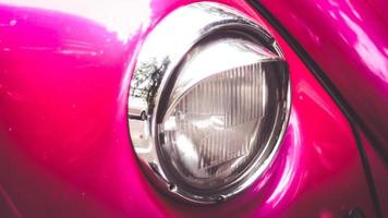primo piano dei fari di un'auto d'epoca rosa foto