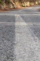 strada asfaltata nera e linee divisorie bianche foto
