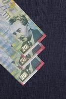 banconote israeliane da venti shekel tra tessuto denim blu foto