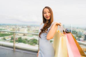 ritratto bella giovane donna asiatica felice e sorridere con la borsa della spesa dal grande magazzino foto