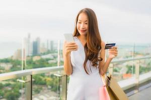 ritratto bella giovane donna asiatica felice e sorridente con carta di credito e cellulare o smart phone e shopping bag foto
