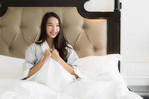 ritratto bella giovane donna asiatica sveglia con felice e sorriso sul letto nell'interno della camera da letto foto