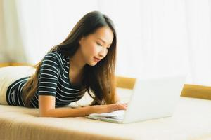 ritratto bella giovane donna asiatica che utilizza computer notebook o laptop sul divano in soggiorno foto