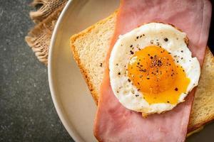 pane fatto in casa formaggio tostato condita con prosciutto e uovo fritto con salsiccia di maiale per colazione foto