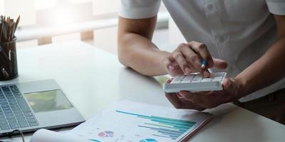 donna d'affari che utilizza la calcolatrice per fare finanza matematica sulla scrivania di legno in ufficio e sfondo di lavoro aziendale, tasse, contabilità, statistiche e concetto di ricerca analitica foto