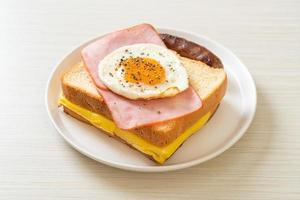 pane fatto in casa formaggio tostato, prosciutto cotto e uovo fritto con salsiccia di maiale a colazione foto