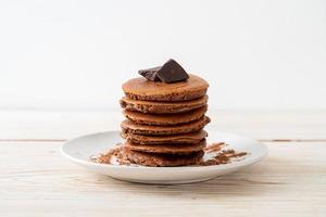 pila di pancake al cioccolato con cioccolato in polvere foto