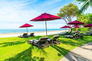 sedie a sdraio e ombrelloni con sfondo spiaggia mare oceano foto