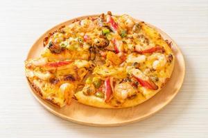 pizza con gamberi, polpo, cozze e granchio su vassoio di legno foto