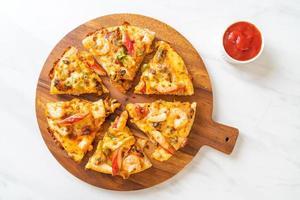 pizza di mare di gamberi, polpo, cozze e granchio su vassoio di legno foto