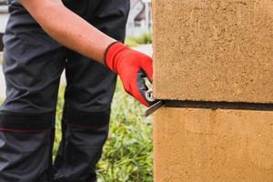 adesivo cementizio per muratura in blocchi di pietra e mattoni in edilizia - un muratore professionista al lavoro foto