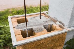 costruzione di un pilastro di pietra da blocchi di cemento - struttura portante di una recinzione in mattoni foto