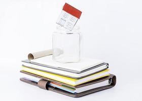 carta a casa in un bicchiere vuoto su una pila di libri foto