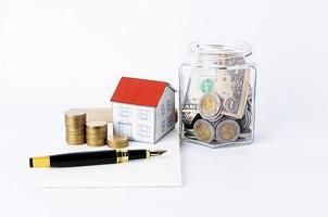penna stilografica con pila di monete e casa di carta e banca di bottiglie foto
