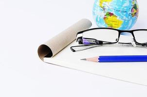 primo piano di matita blu con occhiali e carta per appunti con sfera di terra foto