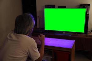 uomo asiatico che guarda la televisione foto