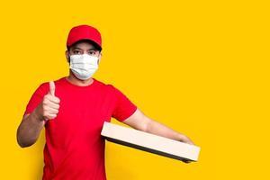 impiegato dell'addetto alle consegne con berretto rosso maglietta bianca uniforme maschera per il viso tenere una scatola di cartone vuota isolata su sfondo giallo foto