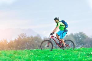 un giovane maschio in sella a una mountain bike all'aperto foto
