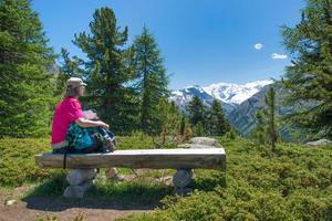 una donna anziana si riposa durante un trekking alpino foto