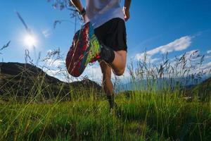 correre in montagna nel prato con sole e splendidi paesaggi naturali foto