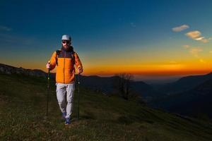 giovane con barba che pratica nordic walking in un tramonto colorato foto