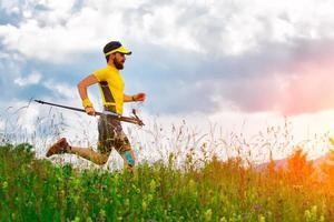 uomo runner con le racchette in mano giù nei prati foto