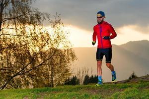 l'atleta corre in montagna al tramonto foto