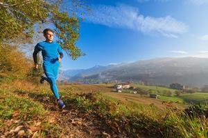 atleta corre su sentiero di montagna in una valle delle alpi italiane foto