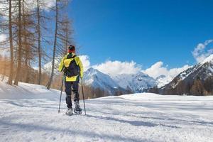 una ragazza cammina con le racchette da neve in solitudine foto
