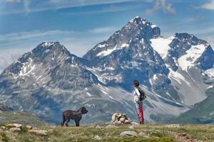 una ragazza con il suo grosso cane nero in montagna ammira il panorama foto