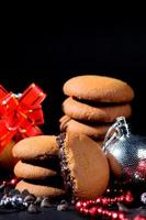 biscotti - pila di deliziosi biscotti alla crema ripieni di crema al cioccolato decorati con ornamenti natalizi su sfondo nero foto