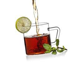 tazza di tè, menta e limone su sfondo bianco foto