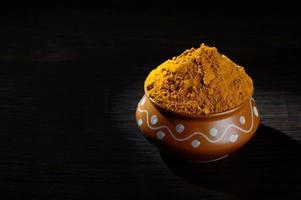 polvere di curcuma in vaso di argilla con radici o cortecce su sfondo nero foto