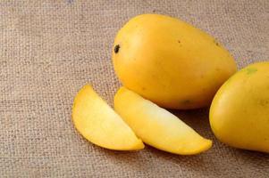 frutta di mango con fetta su sfondo di tela di sacco foto
