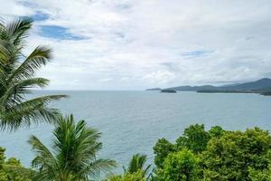 cornice di palme da cocco contro il cielo blu e lo sfondo del mare tropicale foto