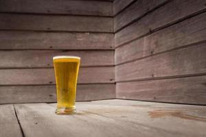 birra di vetro su fondo di legno foto