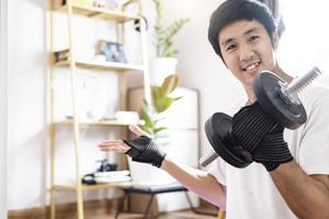 l'uomo caucasico asiatico tiene i manubri in casa foto