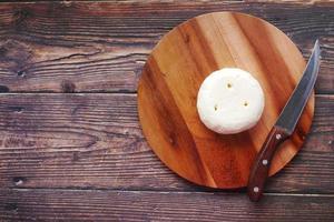 vista dall'alto di formaggio fresco di forma rotonda sul tagliere foto