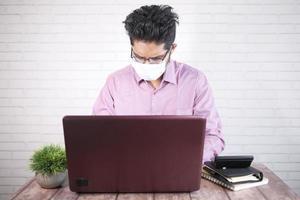 uomo d'affari in maschera facciale che lavora al computer portatile foto