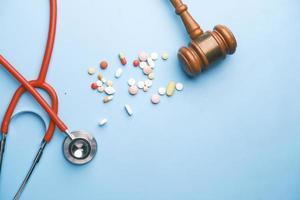 vista dall'alto di martelletto, stetoscopio e pillole su sfondo blu foto