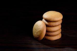 biscotti - pila di deliziosi biscotti alla crema ripieni di crema al cioccolato su sfondo nero foto